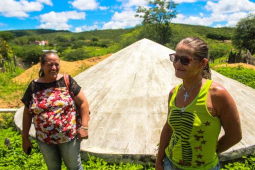 Foto co m duas mulheres em frente à cisterna no sertão